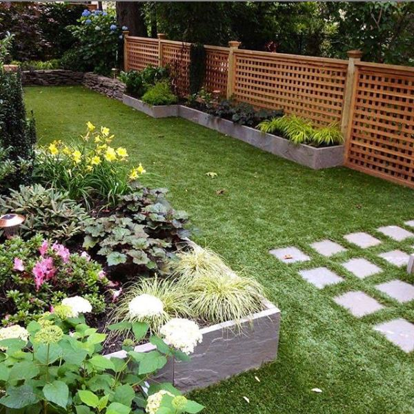 Grass in a Large Back Garden with Paving and Flowers